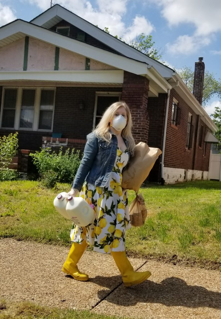 Natalie walks past a brick home carrying two gallons of milk and two bags of groceries, wearing a protective mask and yellow galoshes.