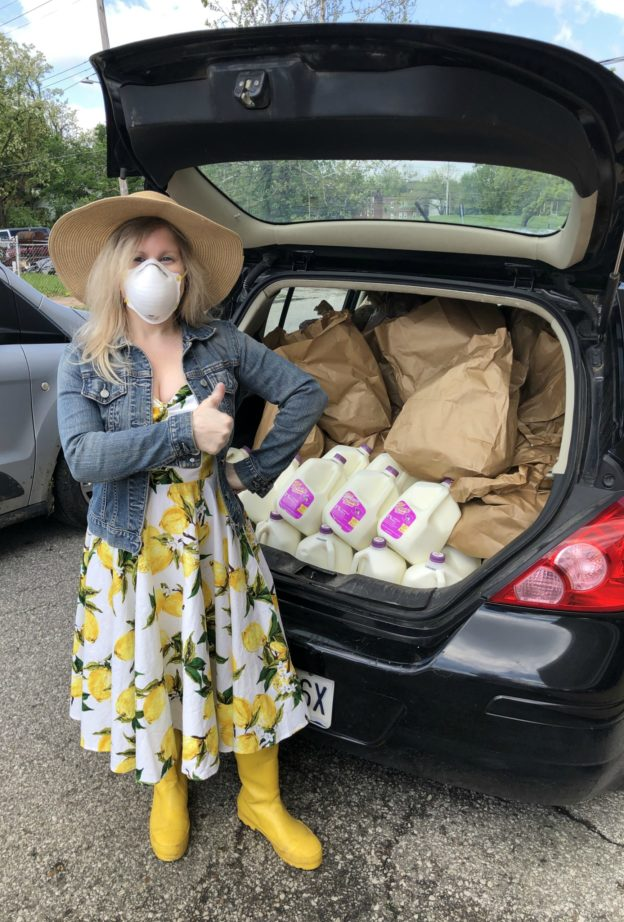 Natalie stands next to a black hatchback full of groceries, wearing a protective mask, giving a thumbs-up.
